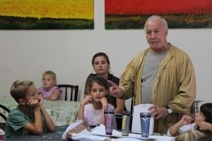 Maler Salvatore Orrù erklärt den Kindern, wie man Farbe mischt.